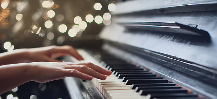 girl playing on an old piano. Beautiful blur background